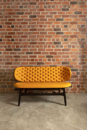 Elegant modern yellow bench with soft back beside brick wall in loft space Zdjęcie Seryjne