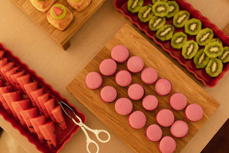 From above appetizing pink macaroons fresh watermelon and sliced kiwi fruit served on cutting boards and red dishes