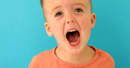 Kid boy brown hair European appearance screams mouth wide open on blue background
