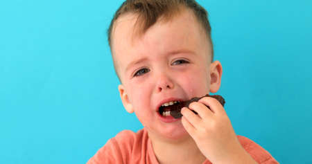 Little boy is upset eating chocolate. The young child is visibly mad or sad on blue background
