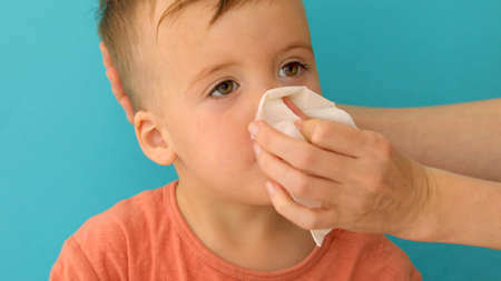 Adult hand holding tissue and help sick boy wiping and cleaning nose on blue background Stockfoto - 129800704