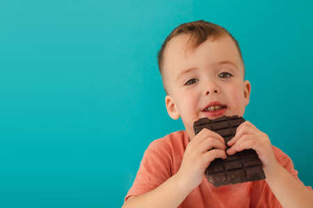 happy boy eating chocolate bar on blue background Stockfoto