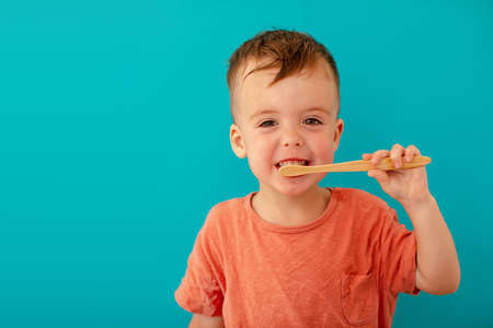 Smiling handsome little boy is brushing his teeth with bamboo eco brush on blue background