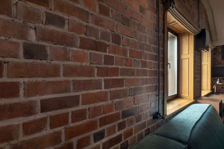 Wall of untreated decorative brick with window indoors with sofas and tables in cafe
