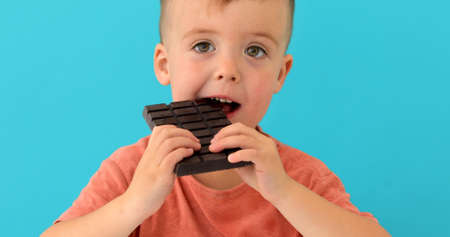 happy boy eating chocolate bar on blue background Stock Photo