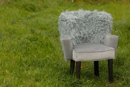 Grey soft chair with fur back on black legs in nature on green lawn Stockfoto - 130628709