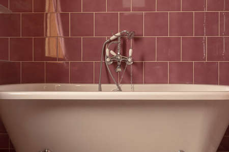 Classic while bathtub with chrome shower head and water tap mounted on red tile wall in bathroom Stockfoto - 130628712