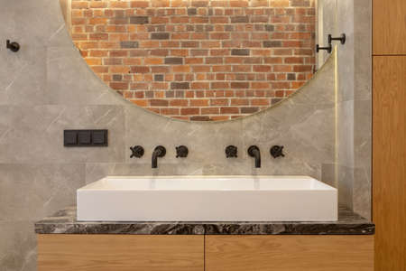Large contemporary bathroom sink with black wall-mounted taps and round mirror reflecting brick wall Stockfoto