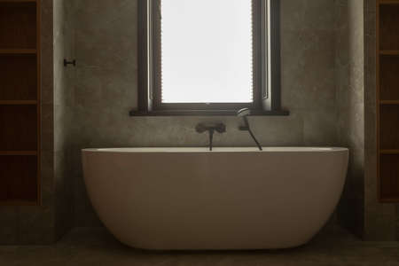 White oval solid base freestanding bathtub with chrome mixer tap and hand shower mounted on wall installed under window Stockfoto - 130628715