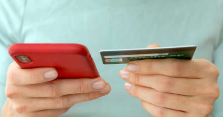 Close-up womans hands holding a credit card and using cell phone for online shopping Stockfoto