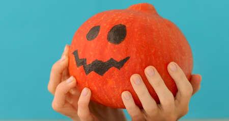 Little orange pumpkin thinks on blue background. Halloween holiday jack pumpkin looking away