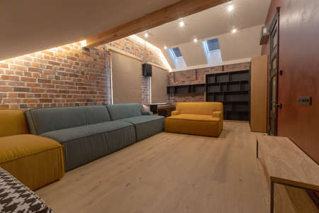 Soft couch and empty bookcase located inside spacious living room with brick walls and blinds on windows Stockfoto