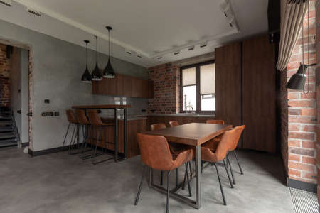 Interior of kitchen with dining table with cozy chairs next to cupboard and counter
