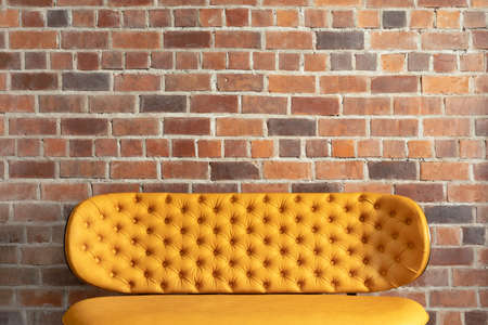 Elegant modern yellow bench with soft back beside brick wall in loft space Stockfoto