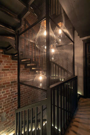 Bright large pendant bulbs glowing among circular stairs against red brick wall in corridor of high rise building with loft style interior