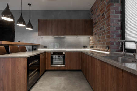 Contemporary interior design of light clean spacious kitchen with brown wooden furniture set in composition with bar chairs at counter and appliances against gray stucco and brick walls in loft style Imagens