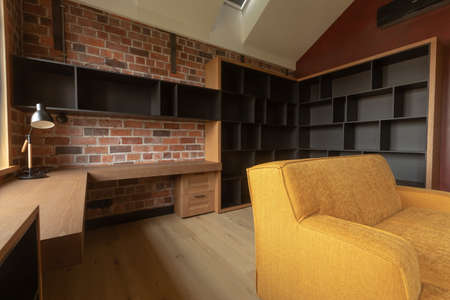Contemporary interior of light spacious living room with brown and black wooden furniture and yellow sofa against red brick walls under attic ceiling with roof window in loft style