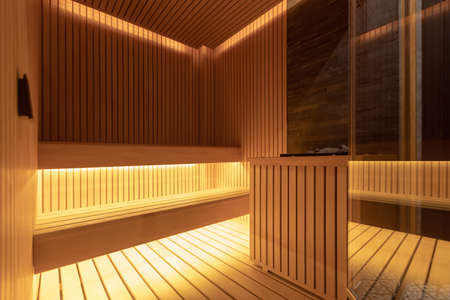 Interior of cozy Finish home sauna with wooden benches and panels in soft light
