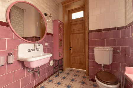 Interior of clean light restroom with retro sink beside big round mirror and decorated cabinet on tall wall with white and pink tile next to toilet bowl with brown lid in apartment