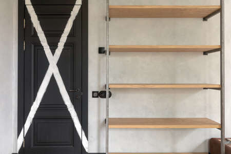 Closed black panel door with painted white cross next to empty wooden book rack against gray plastered wall in light minimalist loft apartment