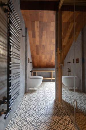 Contemporary interior of spacious bathroom with white toilet bowl and big black radiator on gray wall against shower cabin with glass door in clean light room with attic wooden slope and tile on floor in apartment
