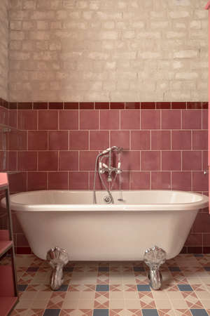 Classic while bathtub with chrome shower head and water tap mounted on red tile wall in bathroom Stockfoto