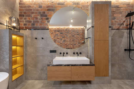 Loft interior of spacious wet room open walk in shower beside cabinet and sink with mirror against decorated built in shelves on gray marble Stockfoto