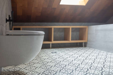 Modern white ceramic toilet bowl and wooden floor shelf in stylish bathroom with window in attic