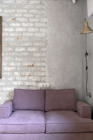 Comfortable pink soft couch with velour upholstery standing against white brick and plastered wall in light loft apartment in daytime Stockfoto