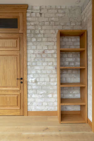 Closed oak panel door with black door knob beside empty bookcase against white brick wall with spots in light minimalist loft apartment
