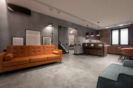 Modern spacious interior of studio flat including brown wooden kitchen with dinning furniture sets and soft orange couch with gray armchair against red brick and gray plastered walls in loft style. Stockfoto - 132194189