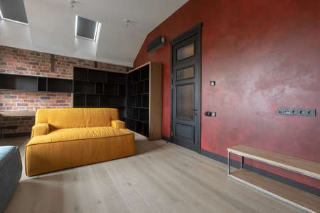 Contemporary interior of light spacious living room with wooden furniture and yellow soft couch against brown brick and red walls under attic white ceiling with roof windows in loft style