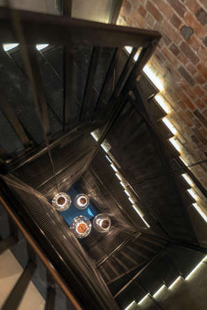 From above black railing and big pendant light bulbs glowing among circular stairs and brown brick walls in corridor of high rise building with loft style interior Stockfoto