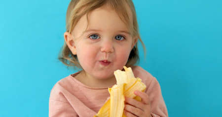 Funny Portrait of a young girl eating banana on a blue studio background Stockfoto