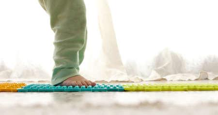 Child on massage mat doing exercises for flatfoot prevention at home