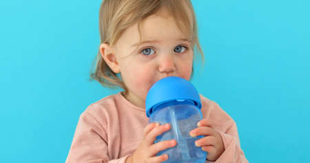 Portrait of a cute toddler drinking water from the bottle. One year old kid holding the baby cup blue background Stockfoto - 132410470
