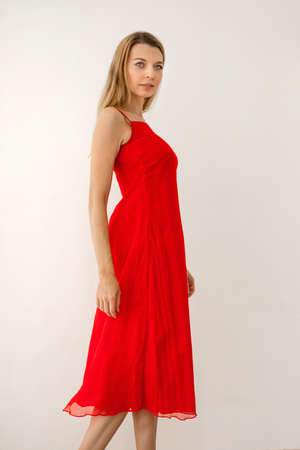 Side view of elegant confident young long haired blonde female wearing bright red midi dress with straps and open shoulders Stockfoto - 132531538