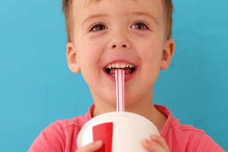Cute little baby boy drinking milkshake blue background