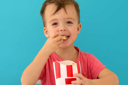 Young boy indoors eating fish and chips smiling blue background Stockfoto - 132705871
