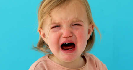 One-year-old baby girl cries blue background. Girl has milk teeth growing