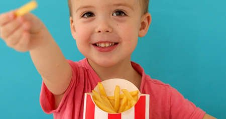 Happy cute boy smiling and offering tasty french fries to camera while eating snack against blue background Stockfoto - 132741870