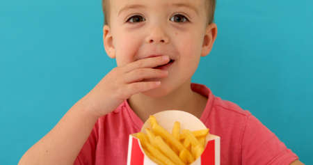 Young boy indoors eating fish and chips smiling blue background Stockfoto
