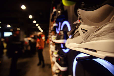 White sneakers on street window of night city decorated with illumination and neon lights