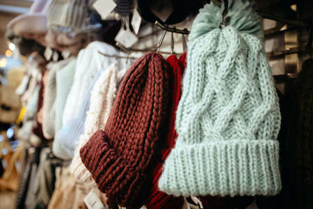 Light blue burgundy knitted hats with pompoms on hangers selling in shop