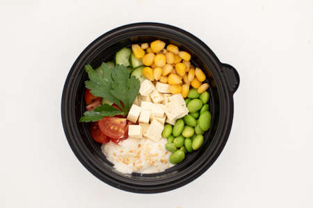 Top view of bowl of fresh beans and vegetables with tofu and sauce poke isolated on white background Stockfoto