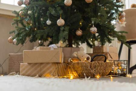 Festive decorated Christmas tree and boxes of gifts in craft paper basket with soft toy and burning light in room Stockfoto