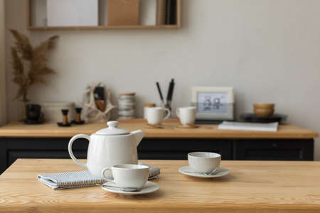 Cute white teapot and white cups on table ready for tea drinking in light kitchen