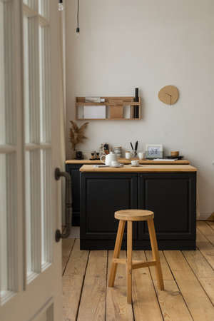 Comfortable light kitchen with table and white tea set reading for tea drinking