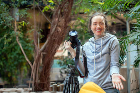 Young satisfied female photographer in casual clothing smiling and looking at camera with green tropical plants on blurred background Stock fotó