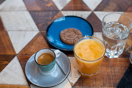 From above of table with cup of espresso cookie on plate and fresh orange juice